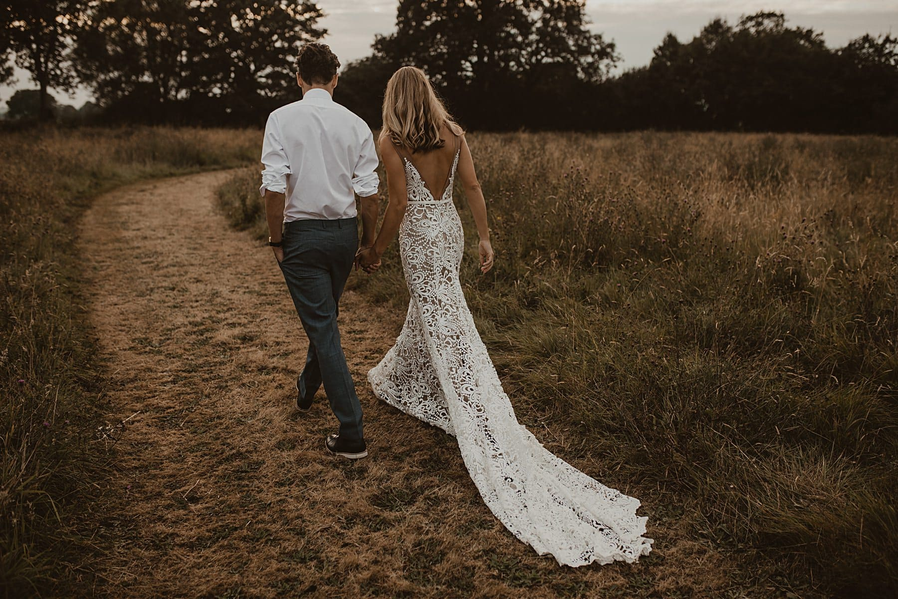 Bride and Groom walking through Meadow