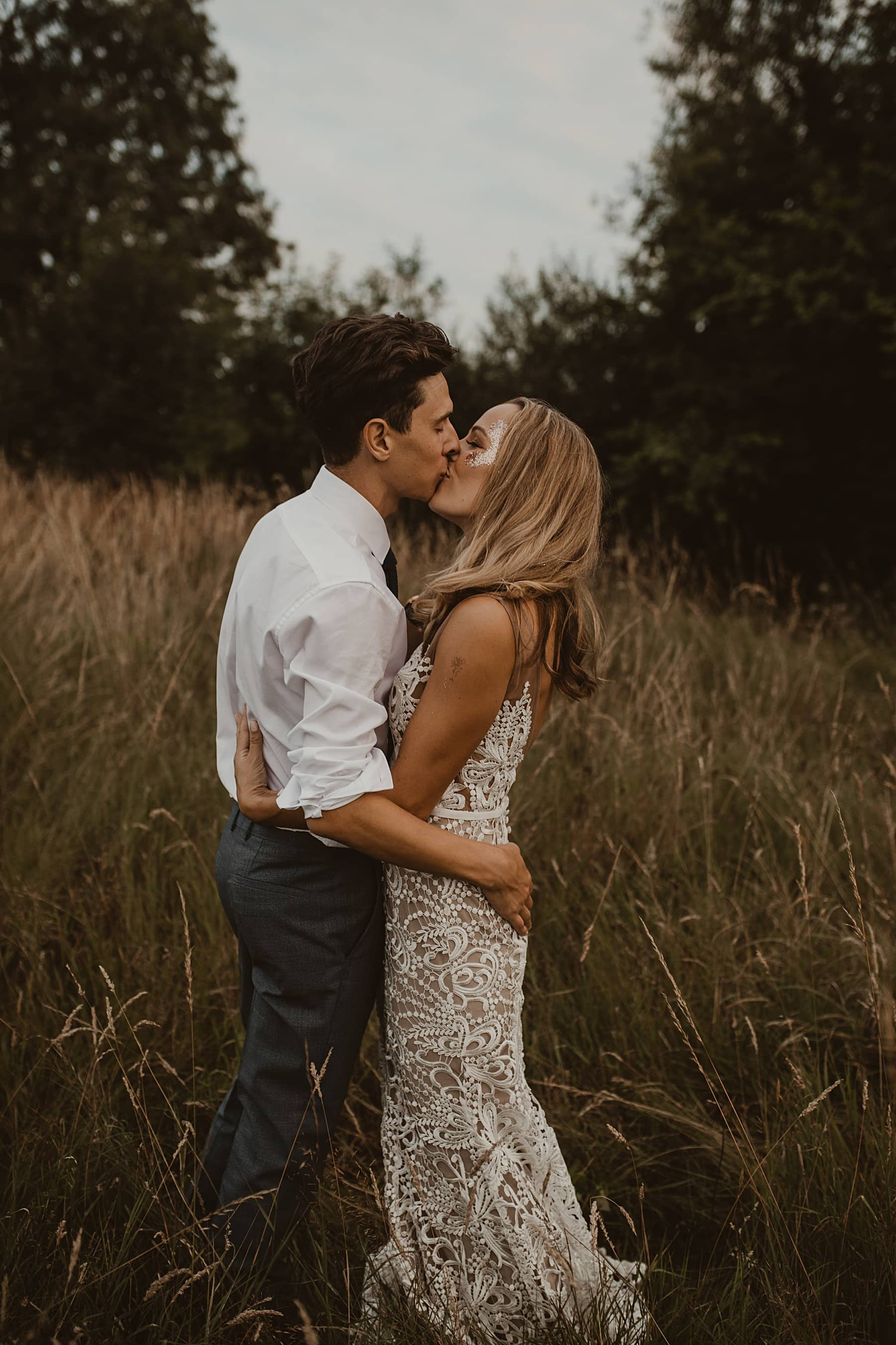 Bride and Groom kissing in wildflower meadow